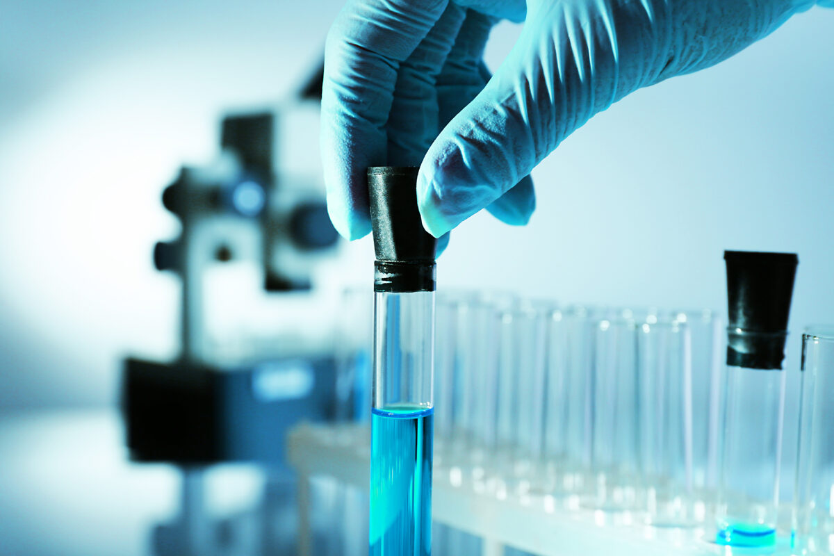 A scientist holding a test tube with blue sample liquid in a laboratory
